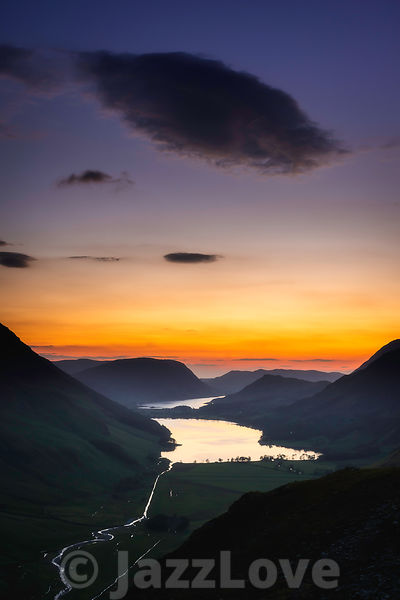 Cloud on evening sky over Buttermere lake and scenic mountain valley in Lake District, Cumbria, UK.