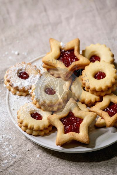Linz shortbread biscuits cookies with jam on linen tablecloth. Flat lay