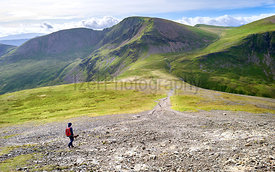 A hiker walking down towards the path leading to Crag Hill and Grasmoor from Hopegill Head in the Lake District, England, UK.