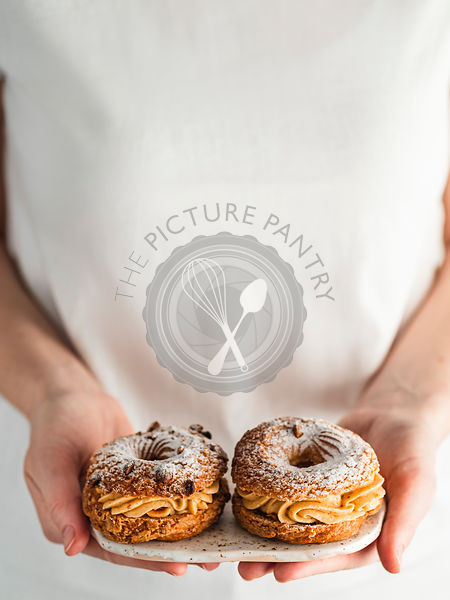 Woman holds two Choux Paris Brest pastry