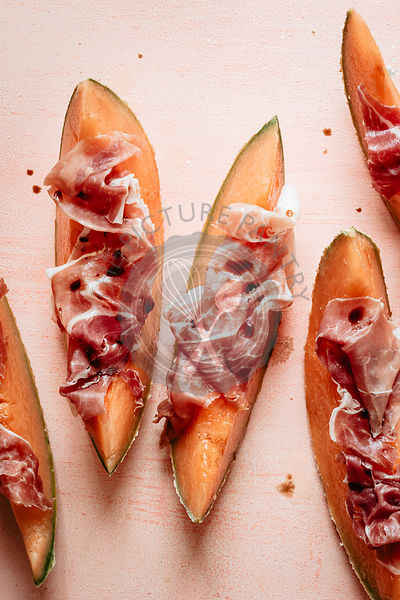 Prosciutto and melone on a orange backdrop
