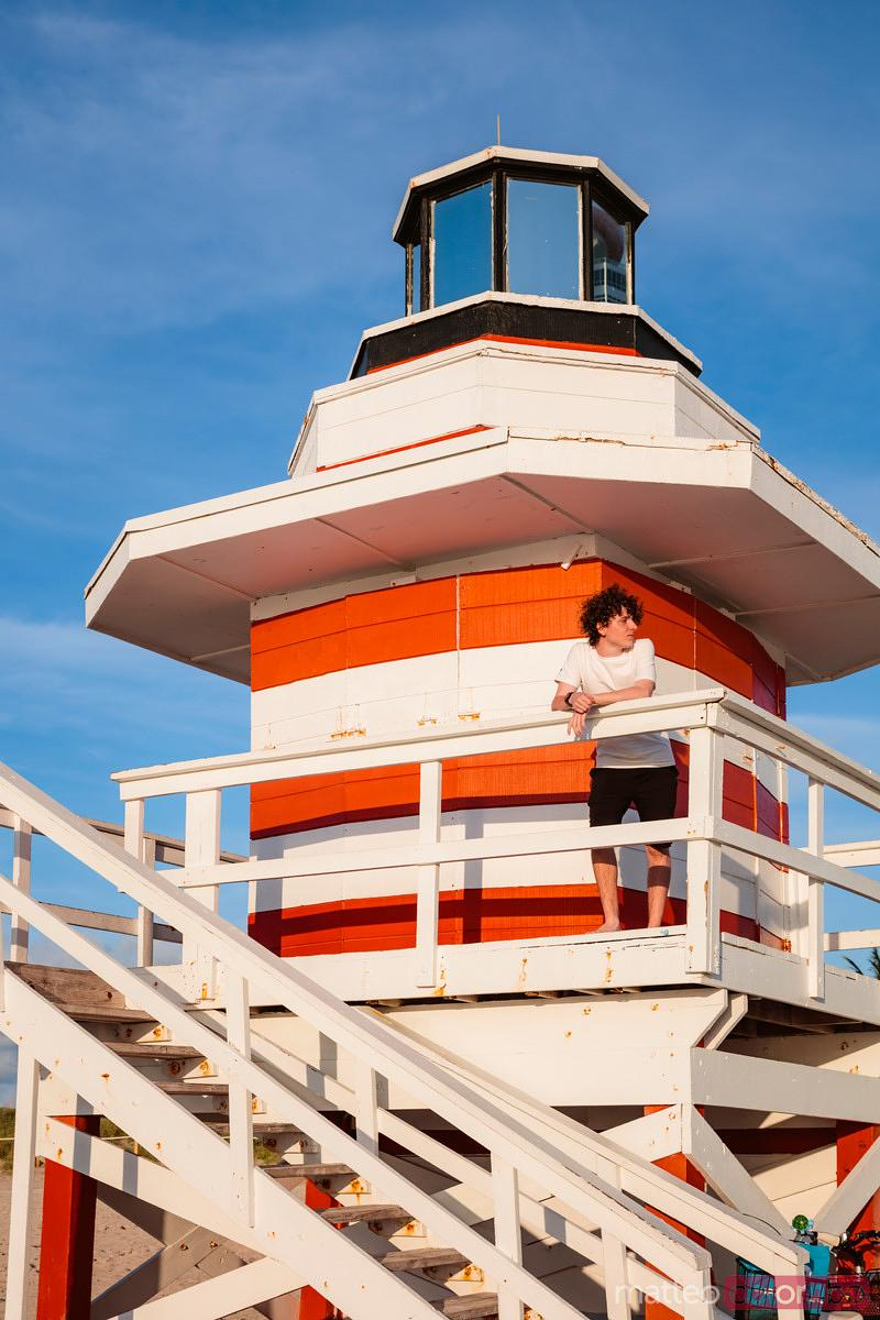Young man on lifeguard tower at sunrise, Miami