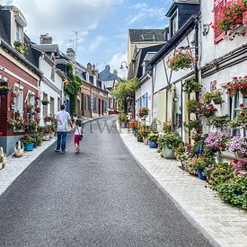 Saint-Valery-sur-Somme, France, August 15, 2020 - Beautiful flowered traditional street Saint-Valery-sur-Somme, Two people ar...