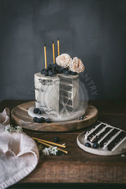 A layer birthday cake with chocolate cake and vanilla frosting, complete with candles.