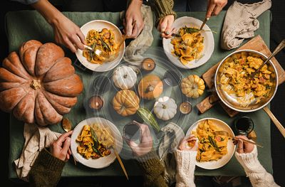 People eating squash pasta with sausage on Thanksgiving day