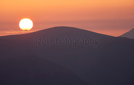 Late evening glow of sunset over the mountains of the Lake District with the sun just about to dip below the ridgeline.