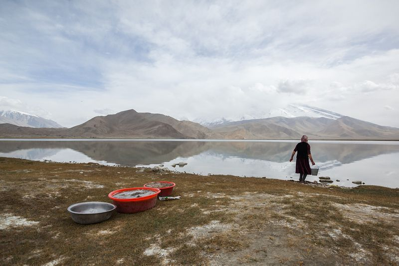 Kyrgyz woman washing clothes outdoor near lake