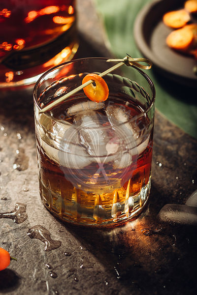 Whiskey with ice and kumquat