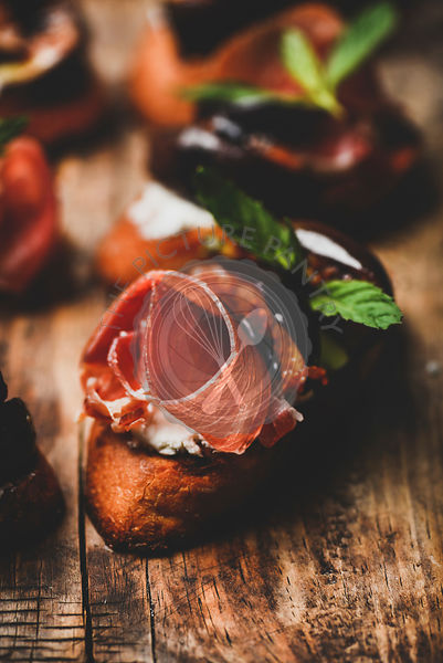 Crostini with prosciutto, goat cheese and figs on wooden board