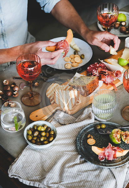 Rose wine, cheese, charcuterie, appetizers and mans hands holding food