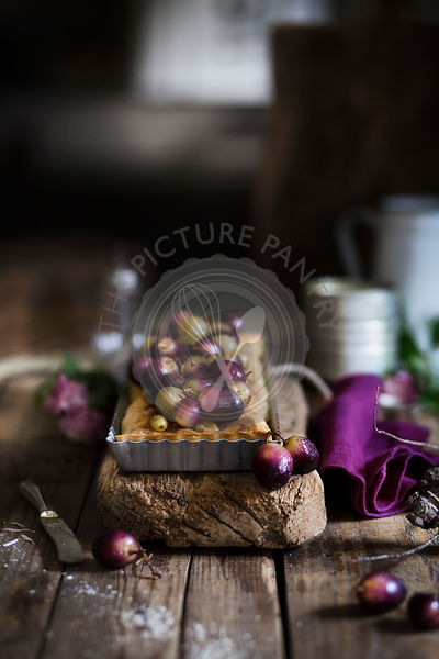 Tart with red and green grapes on wooden table