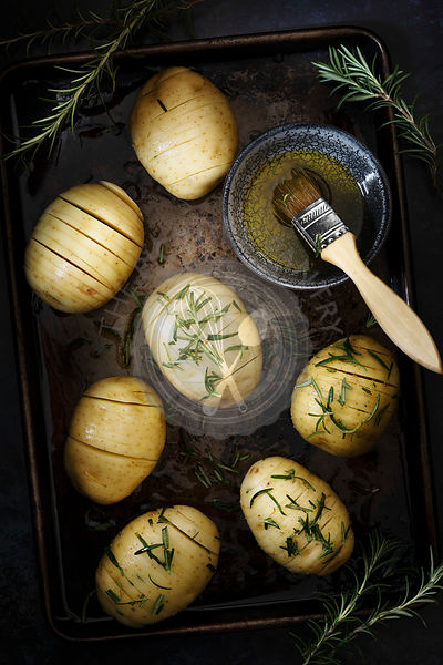 Preparation of hassleback potatoes, brushed with olive oil and sprinkled with rosemary.