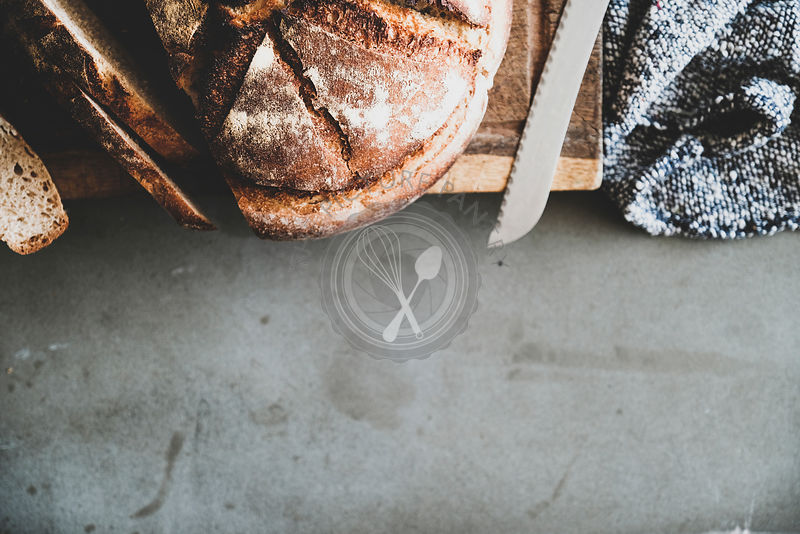 Flat-lay of freshly baked sourdough bread loaf, copy space
