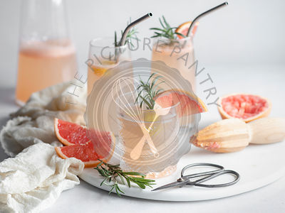 3 glasses of grapefruit cocktail on a marble tray with rosemary and grapefruit slices, pitcher and mousseline napkin