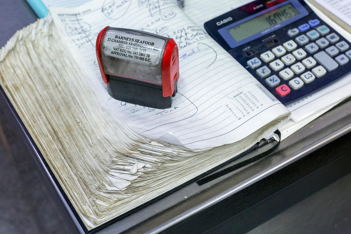 A stamp and calculator on an order book at Barneys Seafood