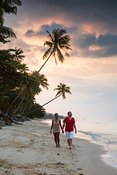 Tourist couple hand in hand on beach at sunset, Thailand