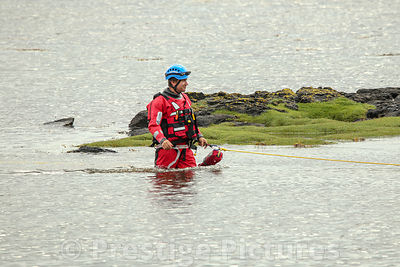 Coastguard officer thigh deep in water during a search