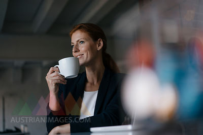 Smiling businesswoman with cup of coffee sitting at desk in office