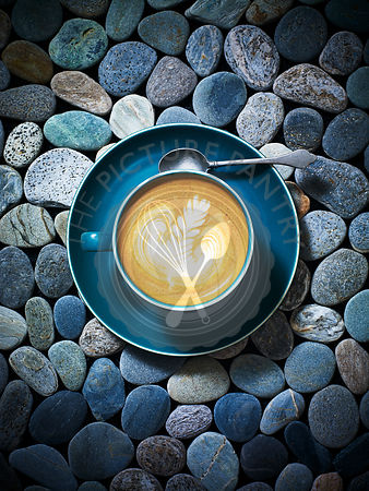 A fresh coffee in a blue cup and saucer with fern pattern in the foam crema froth, against a stone background