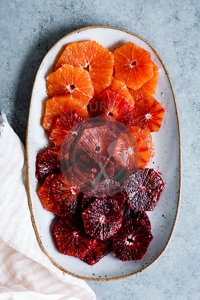 Sliced blood oranges on a ceramic plate