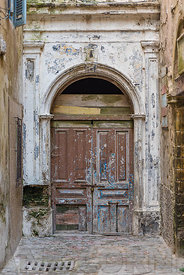 A rustic wooden door and stone of a building in Essaaouira, Morocco.