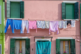 MURANO, ITALY - OCTOBER 25, 2017:  Clothes drying outside a colourful house in Murano, Venice, Italy.