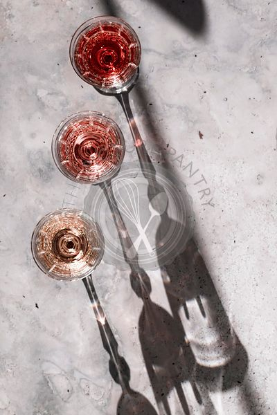 Three shades of Rosé wine in glasses casting hard shadows.