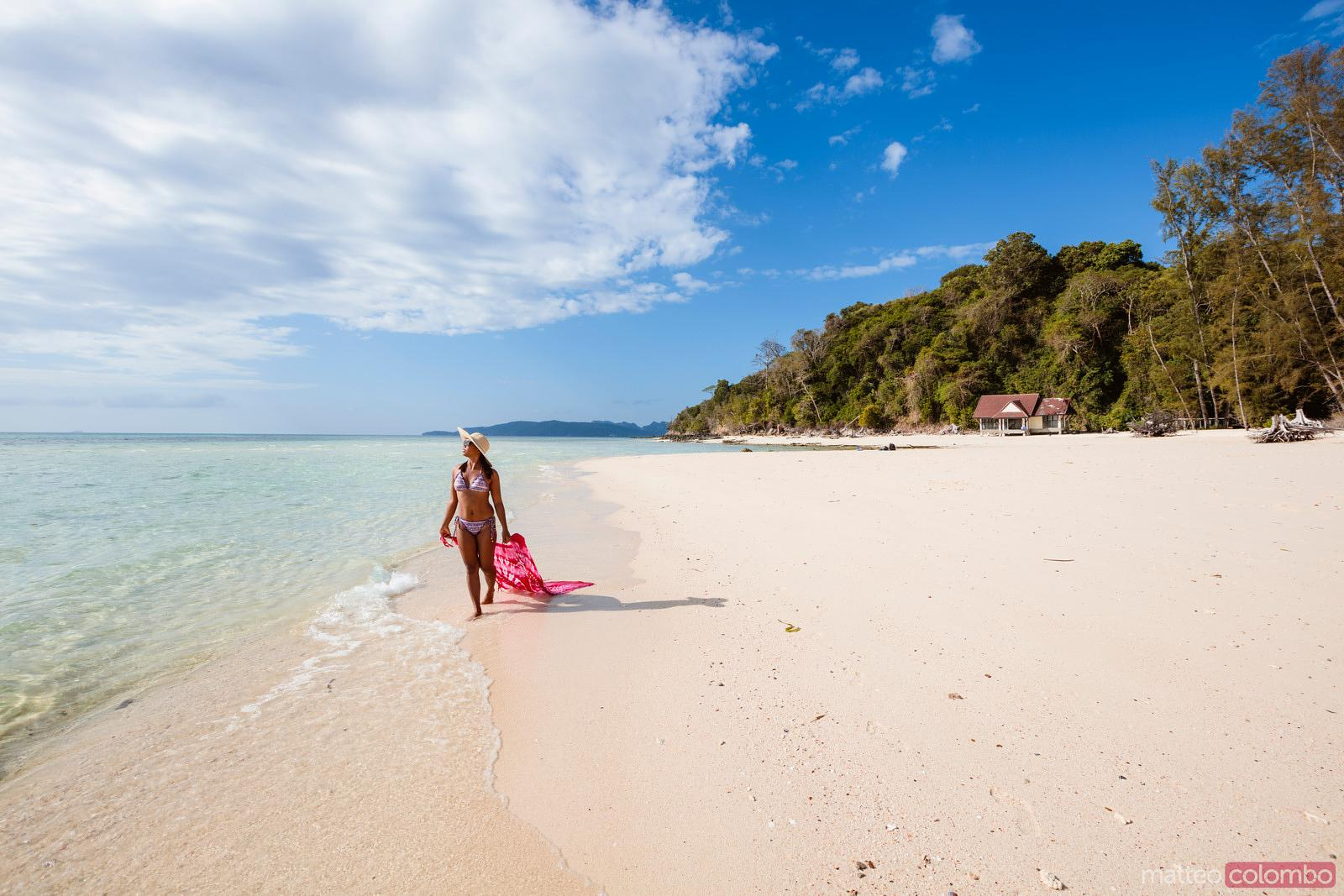 Woman with sarong walking on tropical beach, bamboo island, Thailand