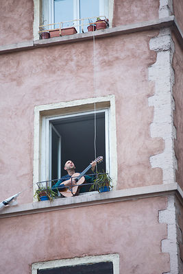 Homme jouant de la guitare tous les soirs à 20h pendant le confinement, rue Leynaud, Lyon, France / Man playing guitar every ...