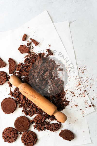 A wooden rolling pin crushing chocolate cookies in preparation for a recipe.