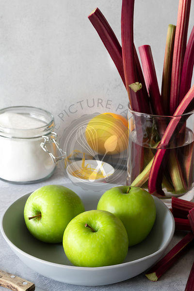 Green cooking apples in a bowl with rhubarb stalks in a glass jug of water.
