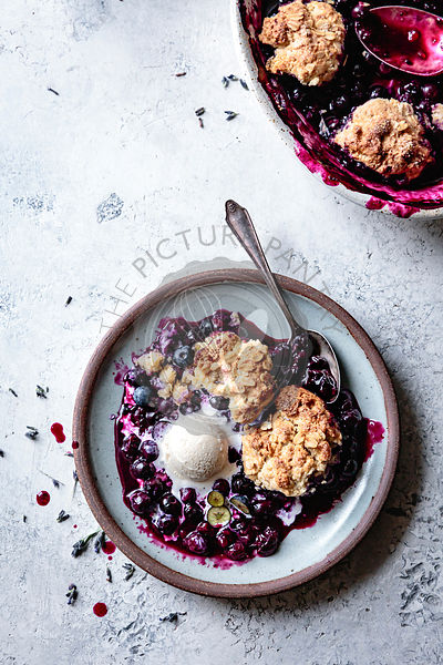 Serving of blueberry cobbler in a bowl with ice cream.
