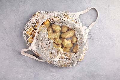Zero waste concept. Fresh organic potatoes in mesh textile bag, flat lay