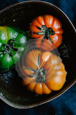 Three colorful tomatoes into the water