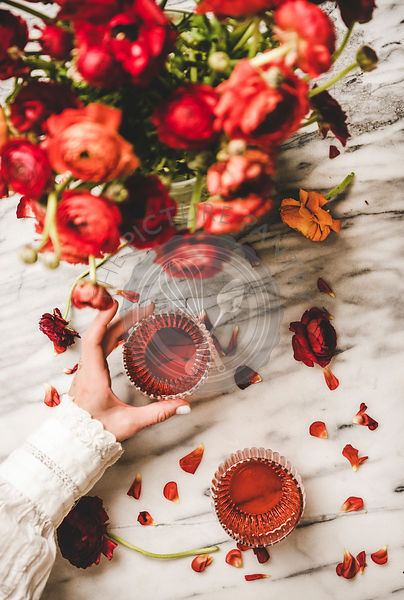 Womans hand holding glass of rose wine and ranunculus flowers