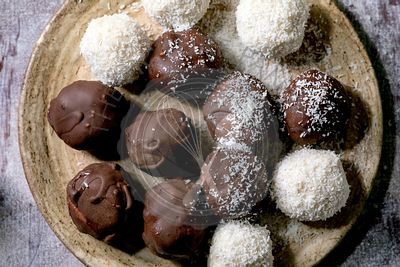 Raw vegan coconut chocolate candy balls over white. Flat lay