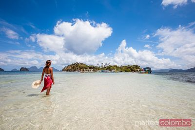 Woman relaxing on a sandbar near island