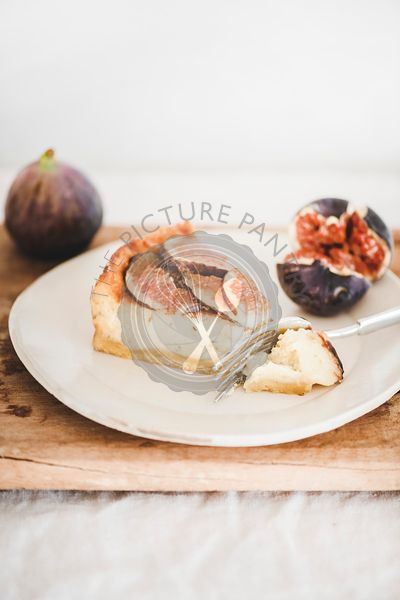 Slice of homemade fig cheesecake with fresh figs on plate