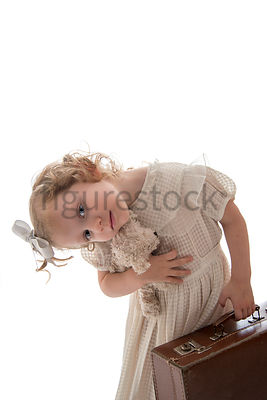 A playful litle girl holding a teddy bear and a suitcase – shot from mid level.