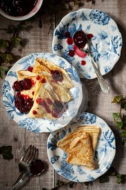 English style pancakes folded onto plates and served with cherry sauce