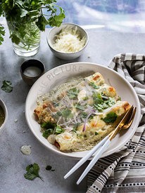Cheesy enchiladas filled with chredded chicken and black beans, served with  creamy sauce