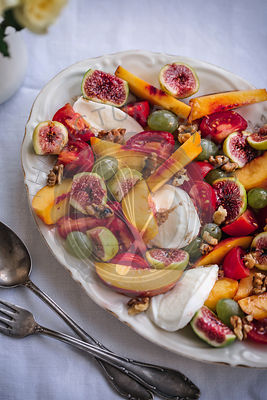 Peach, figs, grapes, cherry tomatoes, mozzarella and walnuts salad on a serving plate