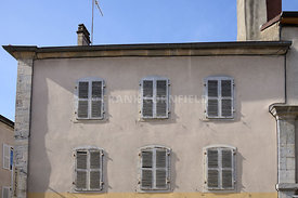 Typical facade of an old apartment above shops in the Frence town of Poligny in the Jura department in Franche-Comté.
