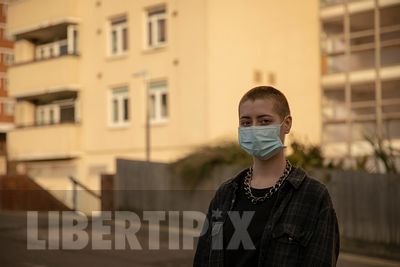 A close-up of one young Generation Z, queer female, outside in an urban setting, in front of apartments wearing a face-mask; ...