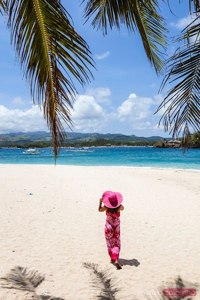Woman with pink sarong walking on beach, Boracay