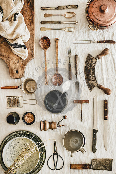 Various kitchen utensils and tablewear over linen tablecloth, vertical composition