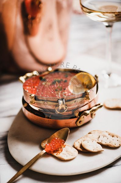 Red caviar with crackers and glass of champaigne on board