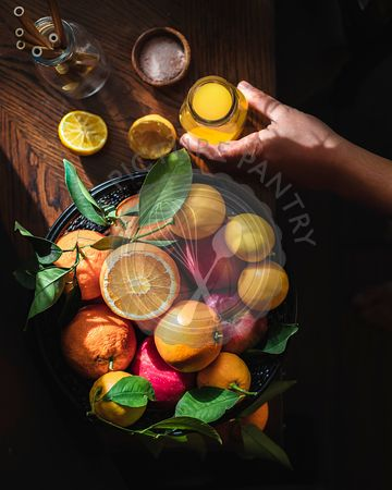 Citrus fruits, including oranges and lemons in a basket.