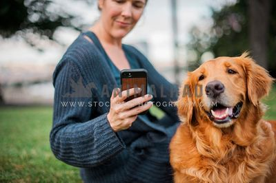 A woman is looking at her phone while sitting next to a golden retriever