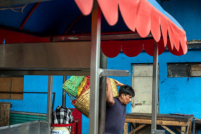 A man carries provisions on his back through the Mercado Terminal